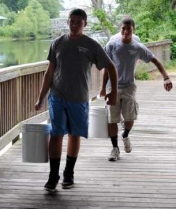 2 guys carrying buckets of water